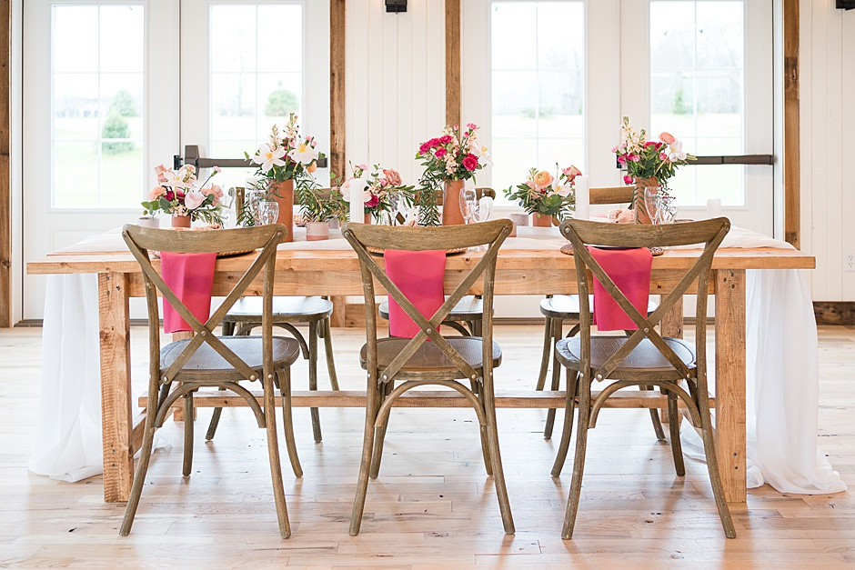 wedding tablescape inspiration with pink flowers, bright colors, white and pink, with barnwood table and wood chairs