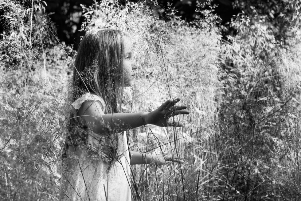Black and white portrait of girl in hifh grass   portrait photography