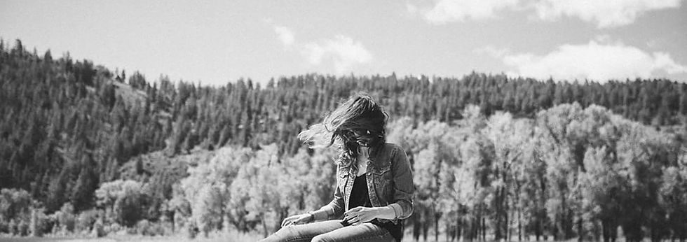 girl on rock writing song