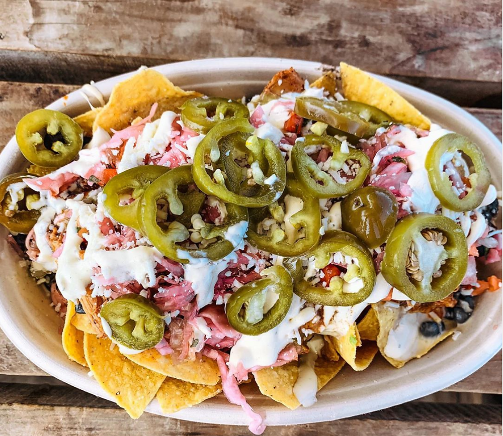 Barrio food cart nachos piled high with queso fundido, jalapeños, crema, pickled cabbage, black beans and fresh salsa.