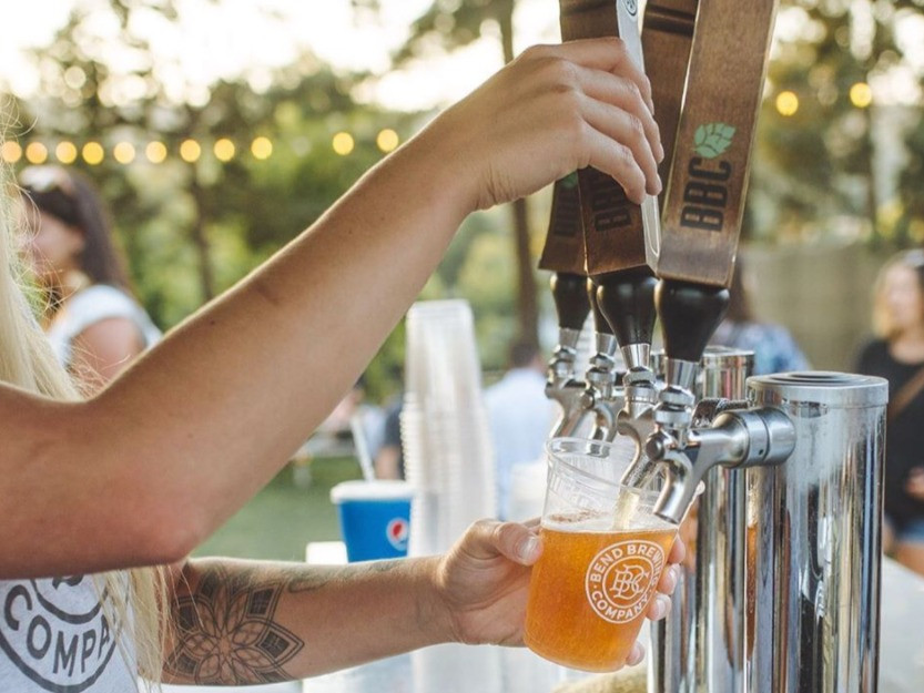 Woman pouring a pint of beer for locals night at Bend Brewing Company in Bend, Oregon