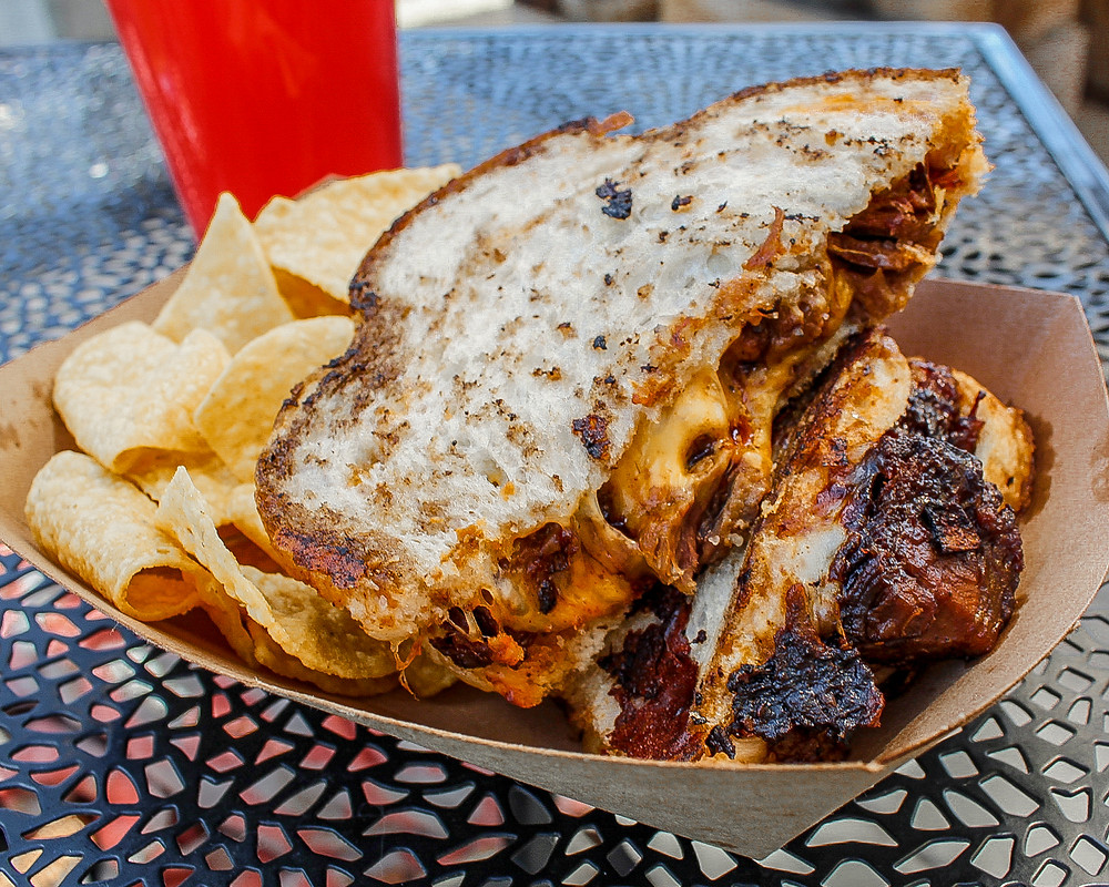 CurbBQ food cart lot's famous brisket grilled cheese, made with sourdough, brisket, four cheeses, homemade barbecue sauce, and served with chips.
