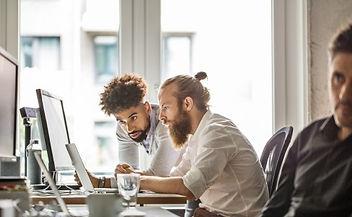 two-men-look-at-desktop.jpeg