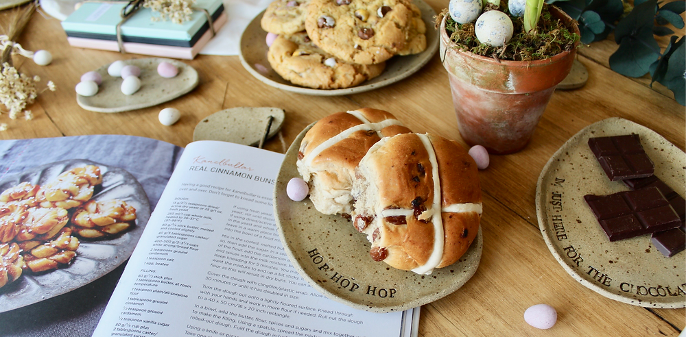 Easter treat table, featuring Scandinavian inspired plates filled with hot cross buns, cookies and more!
