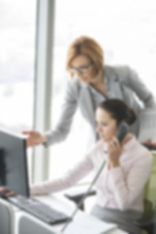 Businesswoman using landline phone while