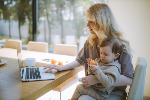 woman-carrying-her-baby-and-working-on-a