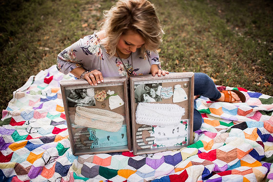 photo of a mother holding shadowboxes which contains cradles, mementos, and photos of her babies