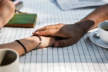 hand-holding-hand-on-the-table-2ETGVWM.j