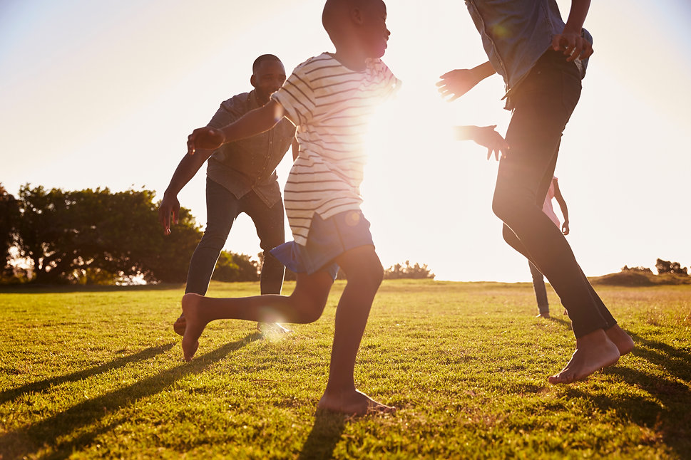 young-black-family-playing-in-a-field-in