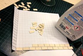 Anfertigung eines Rasters auf einem separaten Stück Papier für die Fliesenverteilung des Sanitärbereichs, Zuschnitt der einzelnen Fliesen aus dünnem Karton