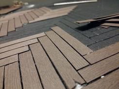 Zuschneiden passgenauer Stücke aus Strukturkarton mit Holzmaserung; Verkleben im eingeprägten Parkettmuster der Bodenplatte
