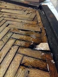 Gießen einer Wasserlake auf dem Bodenstück unter dem Waschbecken