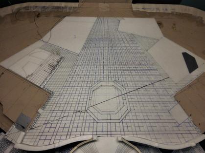 Einprägung des Bodenpflasters der zweiten, erhöhten Ebene. Das Muster verjüngt sich perspektivisch richting Rückwand auf halbe Größe