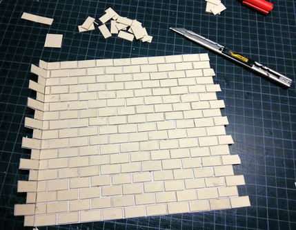Gluing the individual wall tiles to the paper