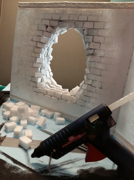 Further stones are glued to the back of the wall element in a circle around the opening