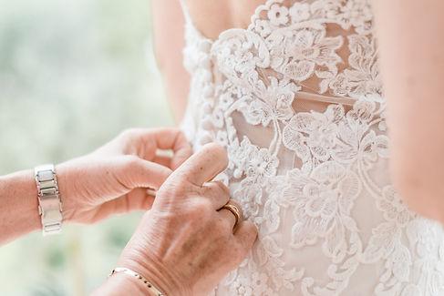 Mutter knöpft Brautkleid zu Hochzeit