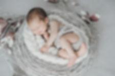 Neugeborenes im Kranz liegend lächelt