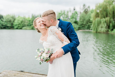 Brautpaarshooting auf einem Steg am Hochzeitstag im Spitzenkleid