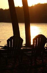 Two Adirondack chairs on a lake at sunset