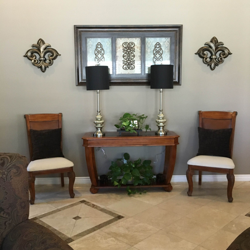 Dining room chairs now flank the entry table to add visual weight. Tall mercury lamps add a reflective elegance.