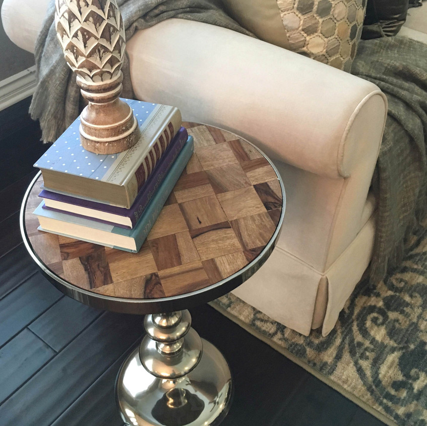 Shiny metallic side tables and colorful hard covered book stacks add interest to a neutral space.