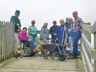 Sefton Coast volunteers clear the sand from the Boardwalk in Formby