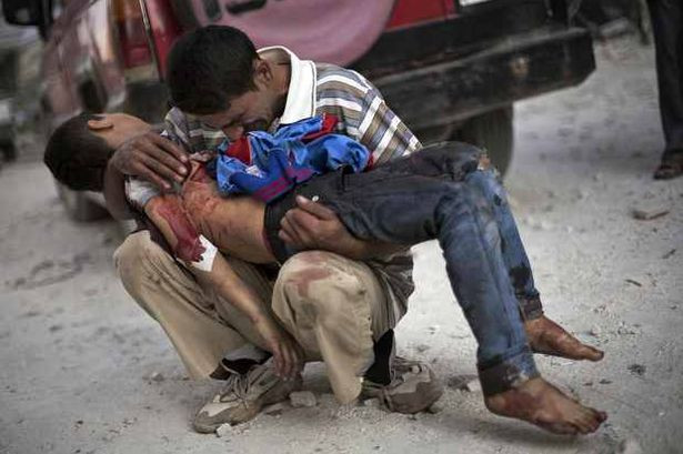 A Syrian man cries while holding the body of his son killed by the Syrian Army n