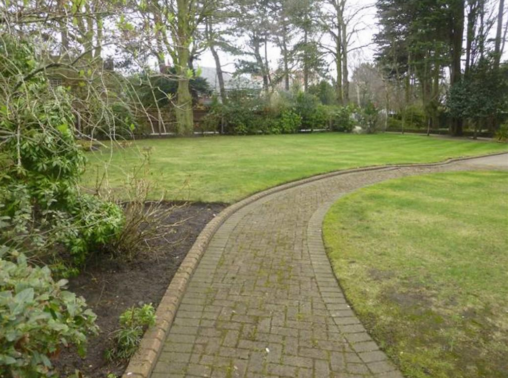 This property is set in mature gardens with a gated tree lined drive.png