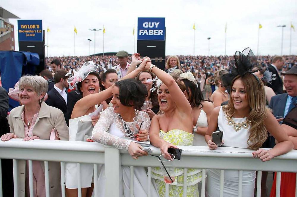 Racegoers celebrate a win during ladies day.jpg