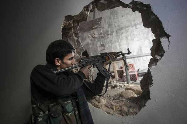 A Free Syrian Army fighter aims his weapon during clashes with government forces