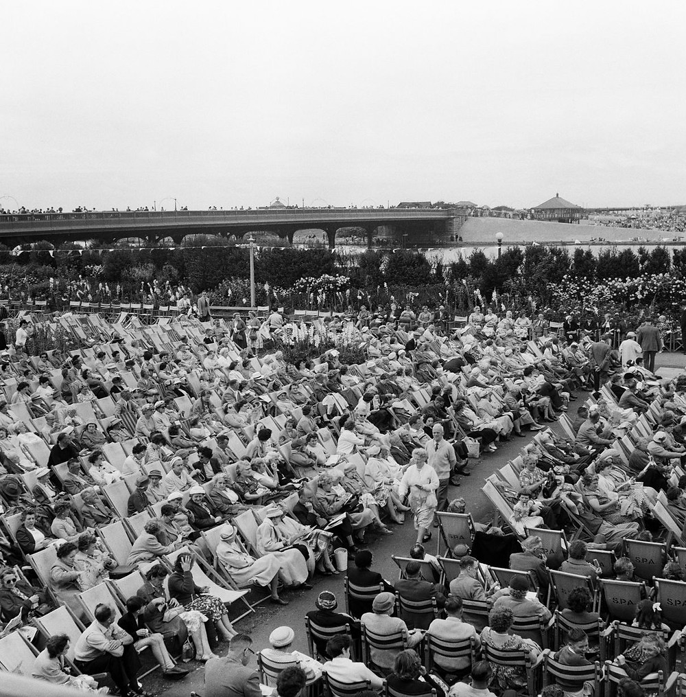 Crowds of people relax in the floral Hall Gardens, Southport, as they listen to