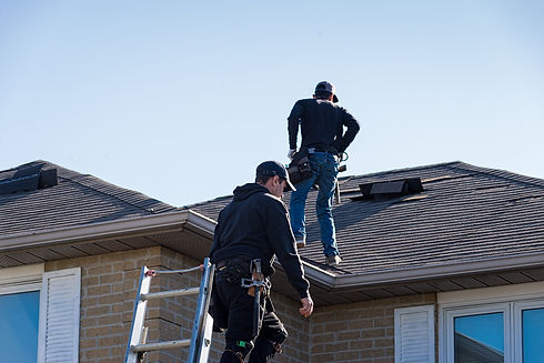 Two roofers inspecting a damaged roof.jp