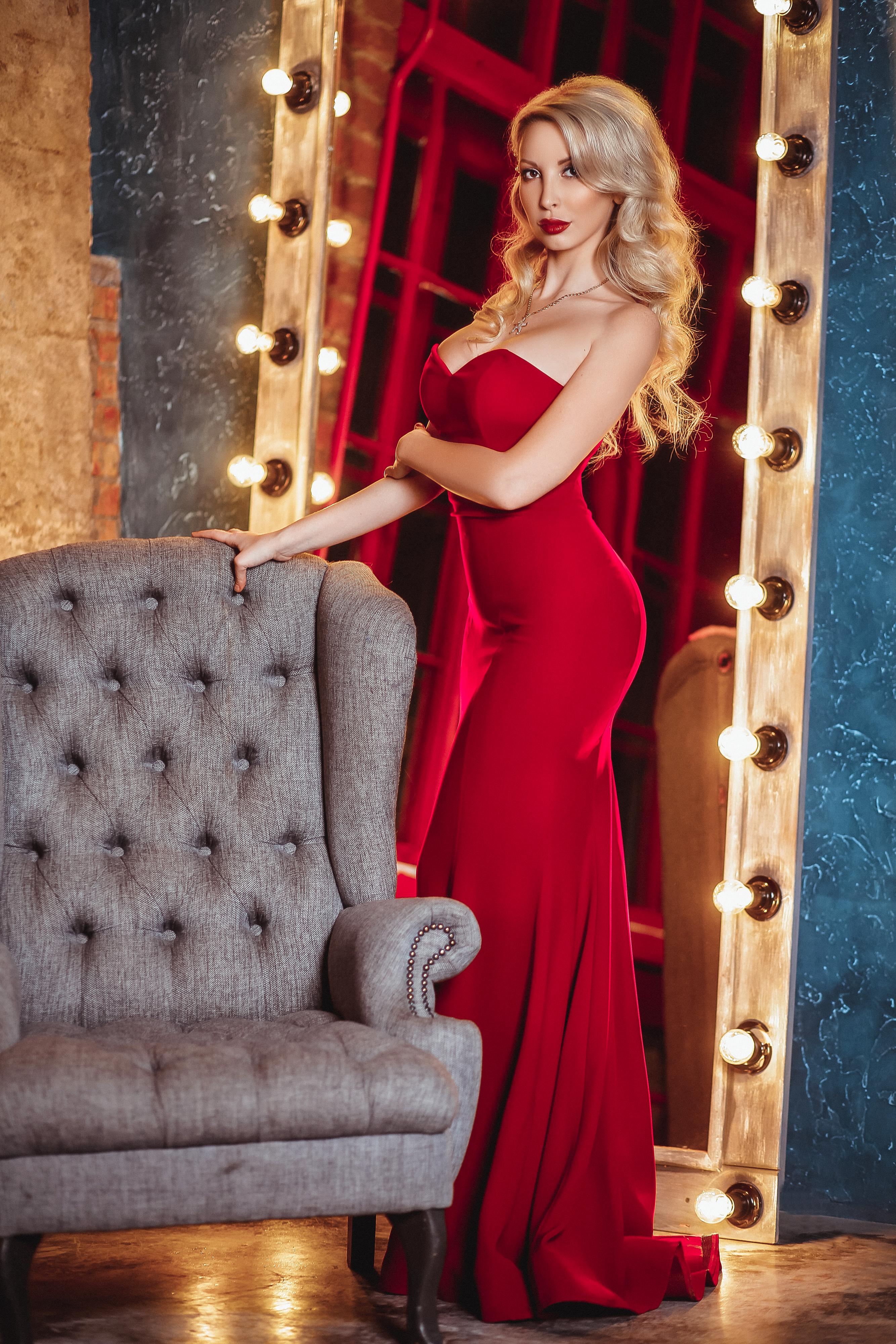 красивая блондинка в красном платье в свете софитов