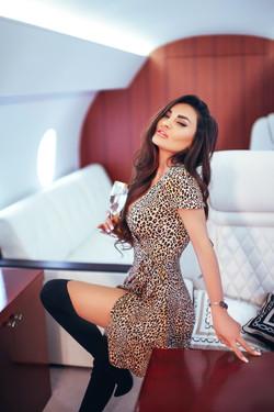 Девушка в леопардовом платье в салоне самолета