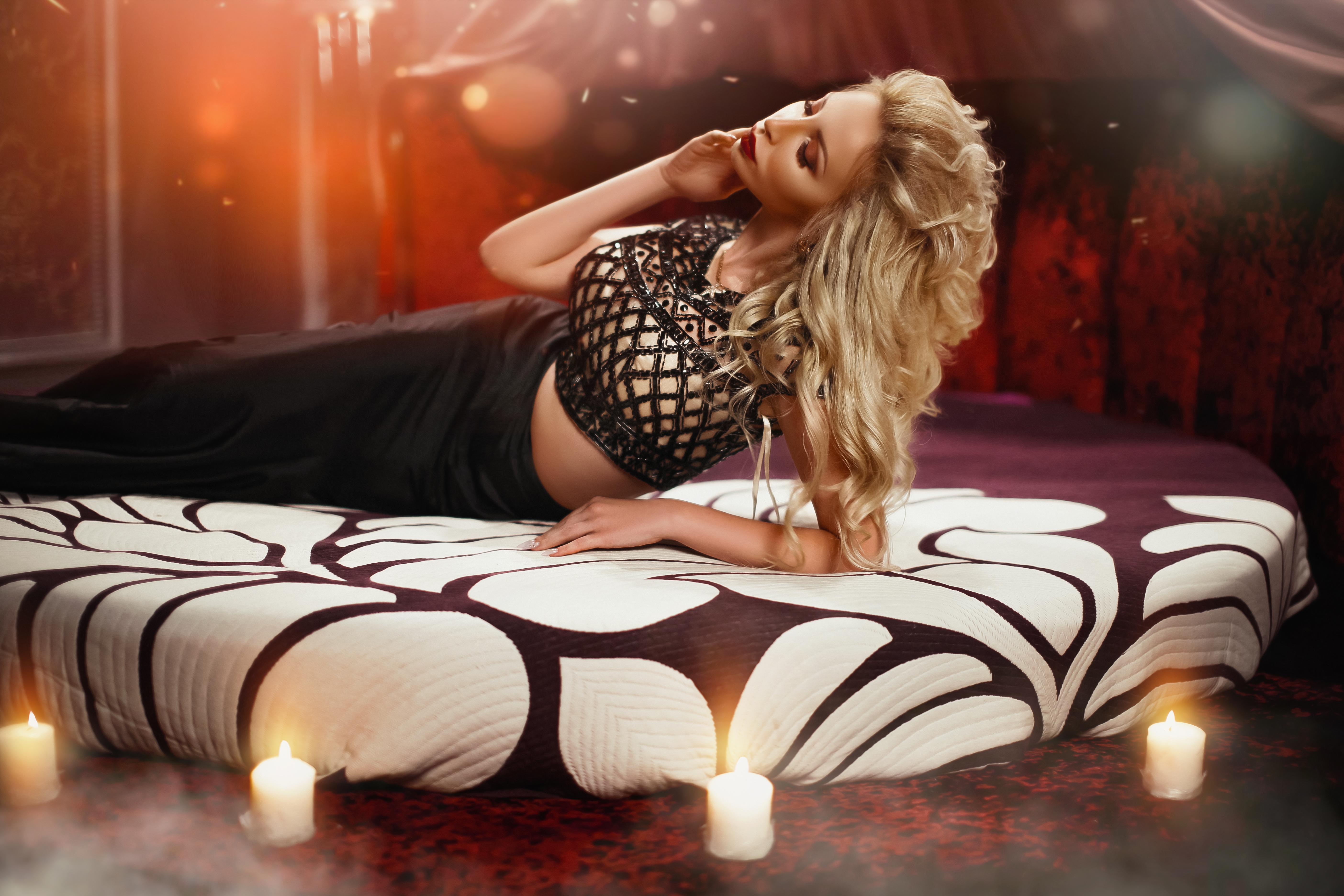 красивая блондинка на кровати при свечах