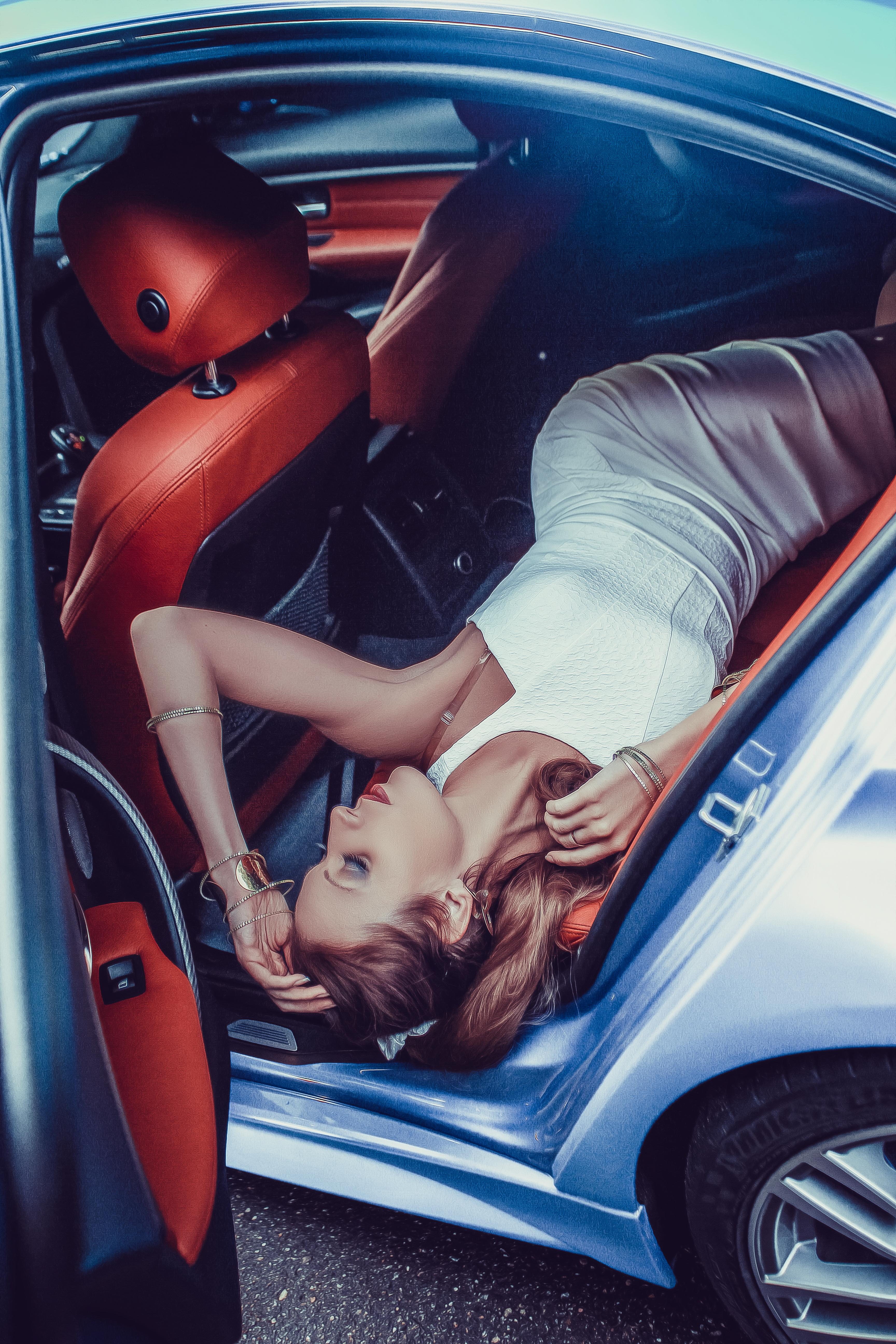 Девушка в белом обтягивающем платье в салоне машины