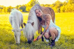 Девушка на лужайке  в окружении милых пони