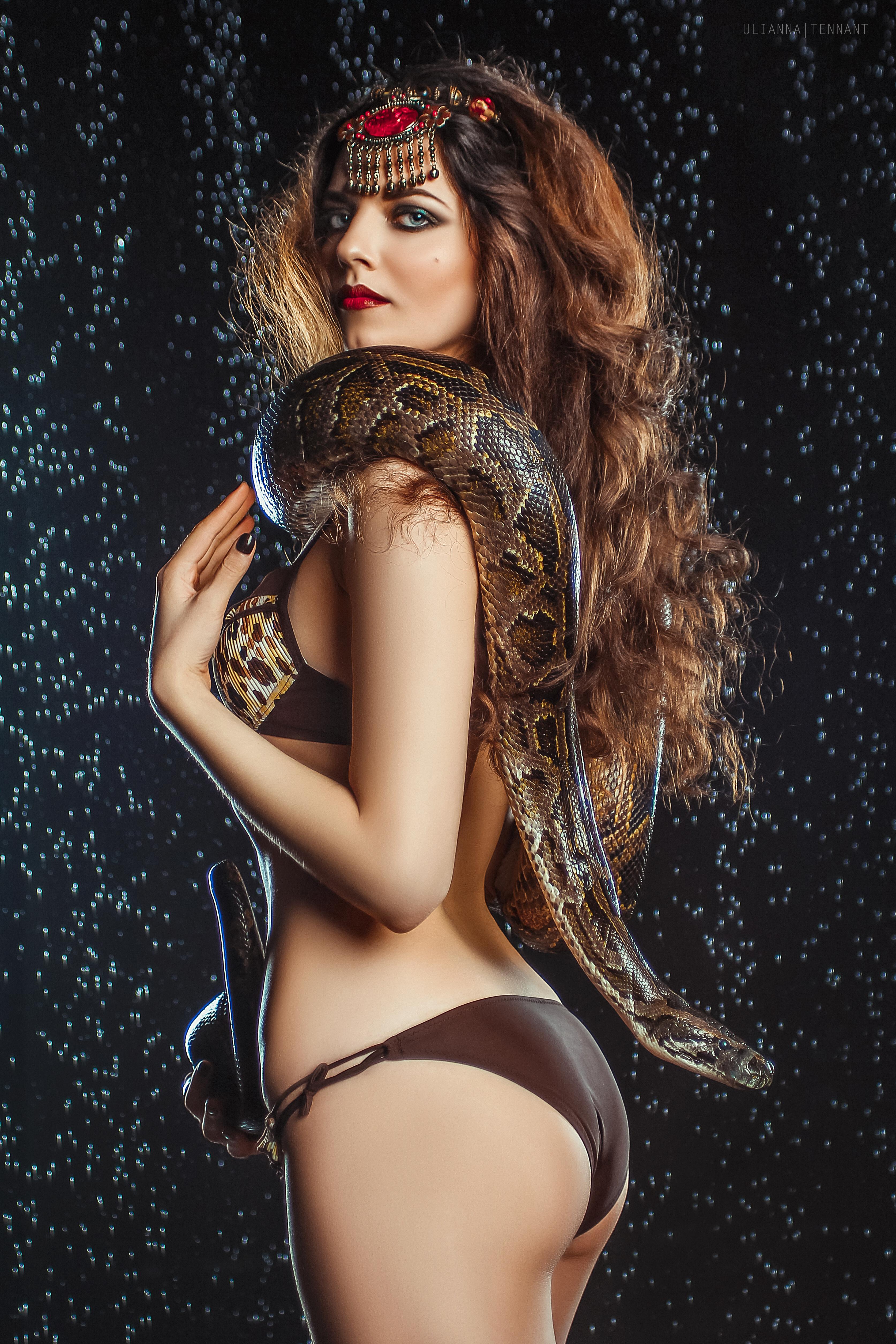 девушка под каплями дождя со змеей в руках