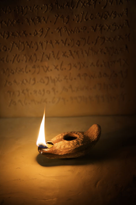 A burning ancient oil lamp with an inscription in the background of the ten commandments w