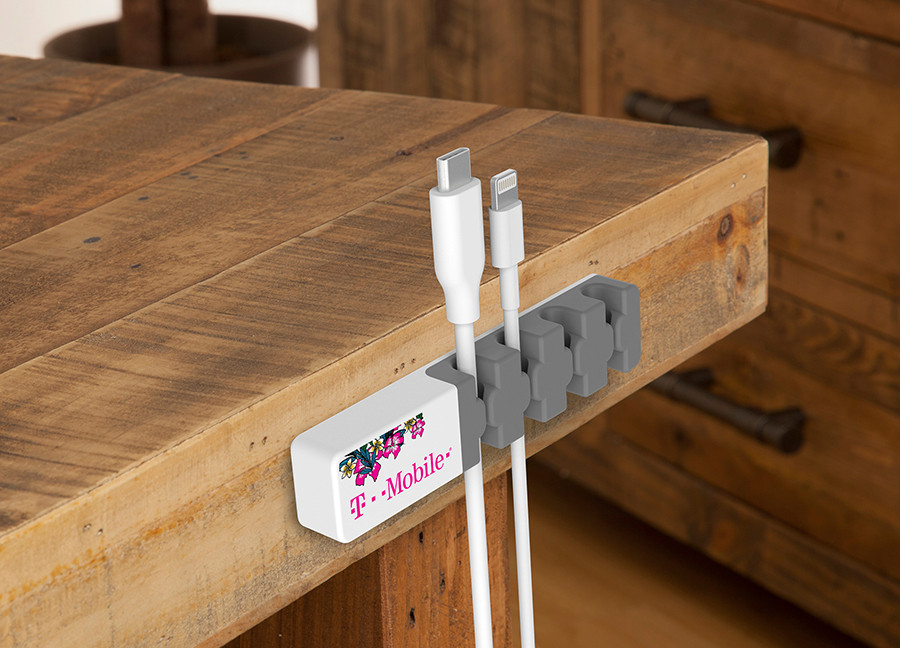 two cords resting in cord organizer attached to side of table