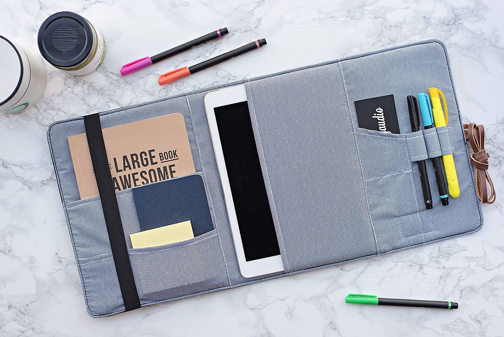 open organizer with notebooks, tablet, pens, and business cards inside