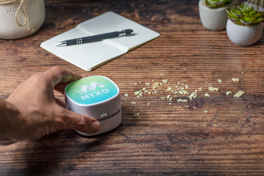 hand using mini desktop vacuum around a line of chip crumbs