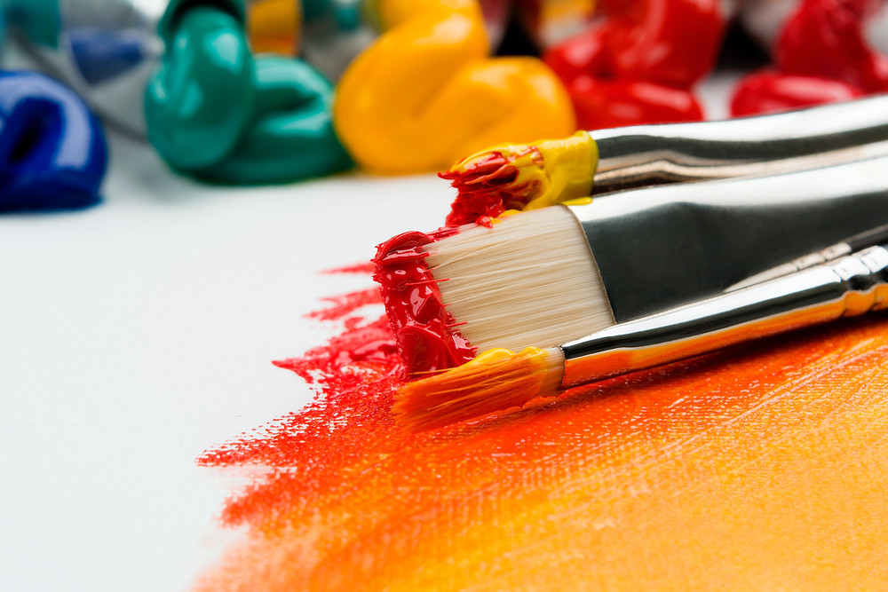 thre-brushes-with-vibrant-red-and-yellow-paint-mixed-to-make-orange-painting-activity
