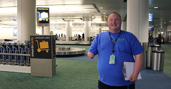 Michael Best pauses for a picture while starting his night shift as a janitorial job coach at Portland International Airport.