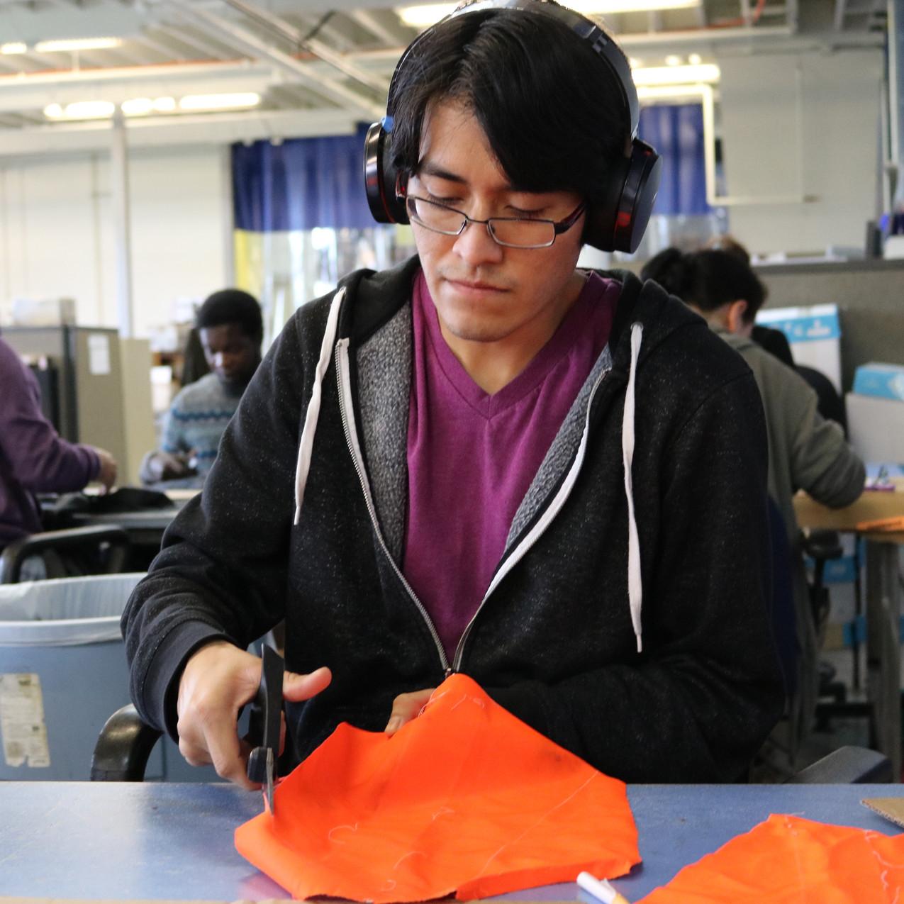 Relay Team Member Cuts Fabric