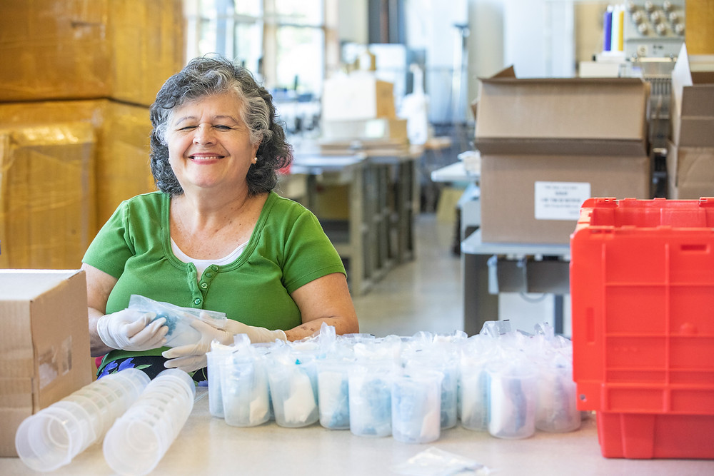 Marta sits at a table filling many plastic beakers with supplies in a bright warehouse space.