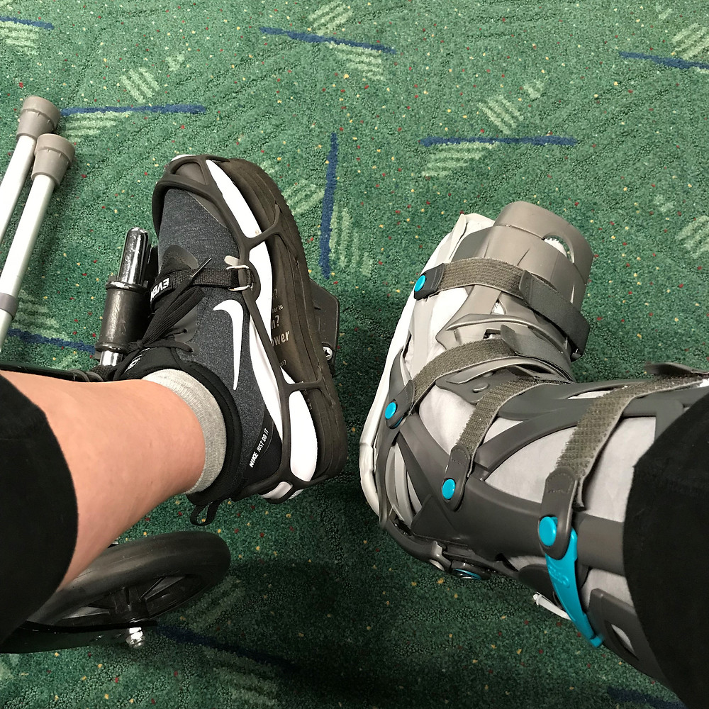 Photo of Tiffini's walking cast boot and shoe riser in front of the PDX airport carpet as she traveled for a conference.