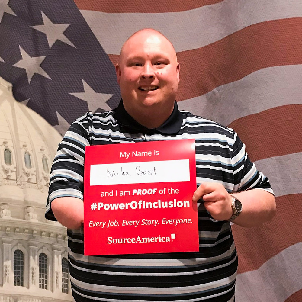 "Mike Best poses with a sign that reads ""My name is Mike Best and I am proof of the #PowerOfInclusion. Every Job. Every Story. Everyone. SourceAmerica"