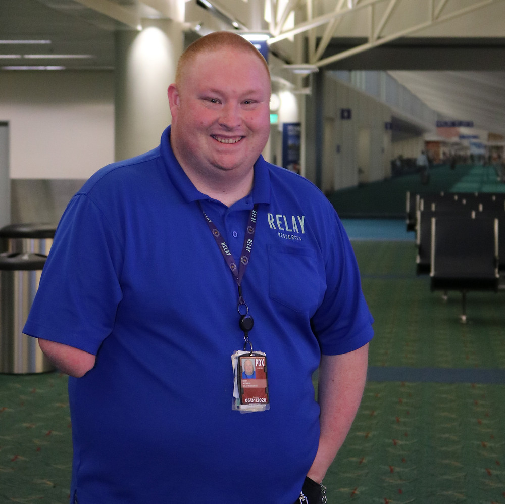 Michael Best stops for a photo after becoming a job coach at PDX airport.