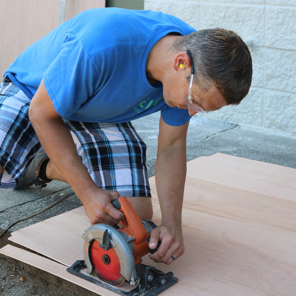 Mason cuts a piece of wood for a Building Maintenance project at a Relay Resources Affordable Housing apartment complex.